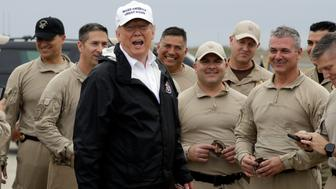 President Donald Trump turns as he talks to U.S. Customs and Border Protection officers at McAllen International Airport as he prepares to leave after a visit to the southern border, Thursday, Jan. 10, 2019, in McAllen, Texas. (AP Photo/ Evan Vucci)