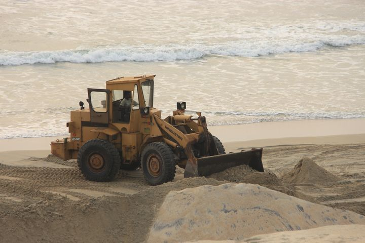 Earth movers in action at Alappad for mineral sand mining.