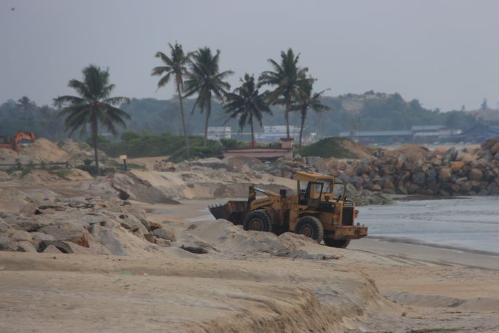 Earth movers digging mineral sand in Alappad.