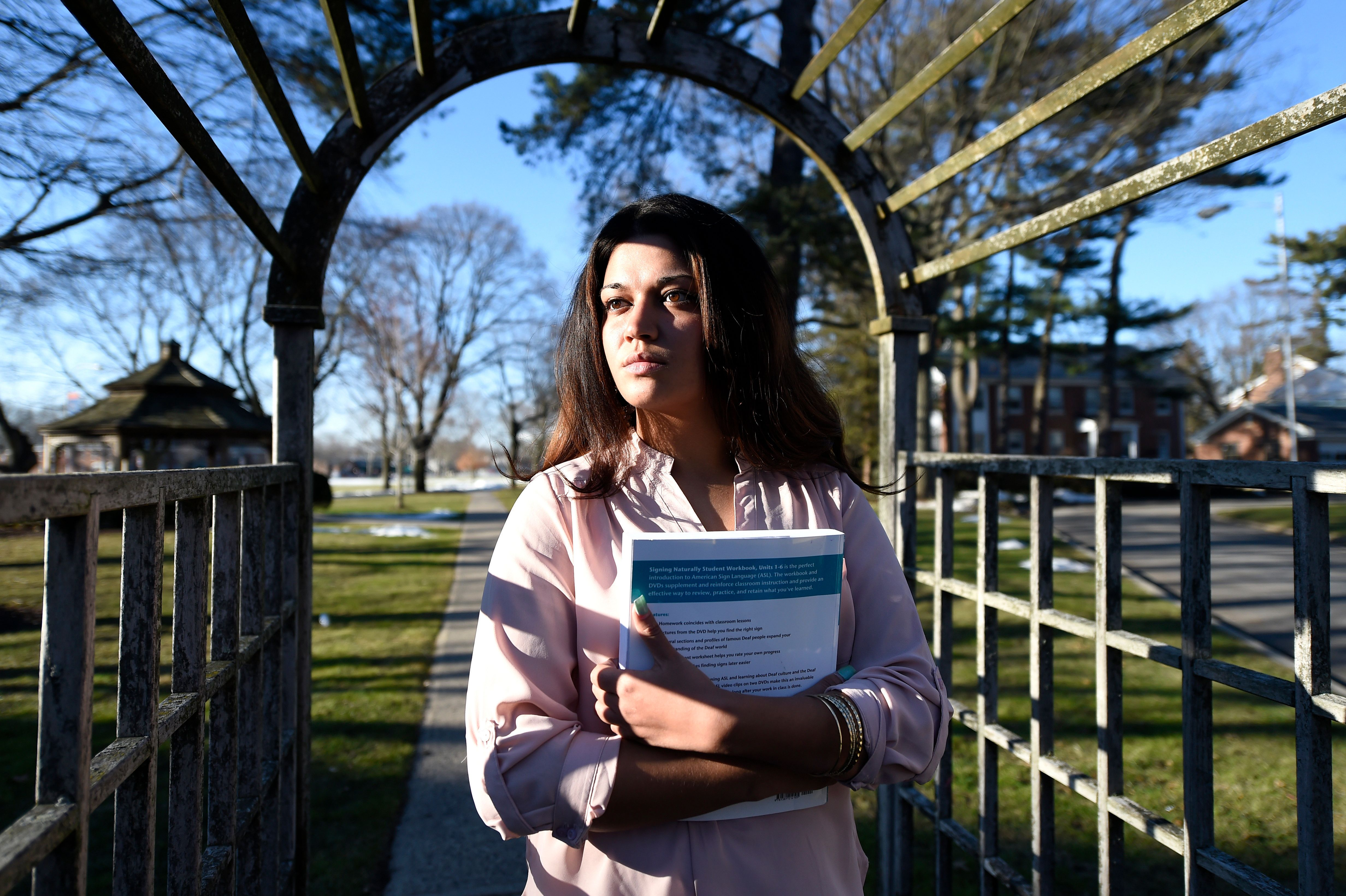 """FILE - In this Feb. 2, 2016, file photo, Naila Amin, 26, holds a book from one of the classes she was taking at Nassau Community College in Garden City, N.Y. According to data provided to The Associated Press, the U.S. approved thousands of requests by men to bring child and teenage brides from another country. """"My passport ruined my life,"""" said Naila Amin, a dual citizen from Pakistan who grew up in New York City. She was forcibly married at 13 in Pakistan and applied for papers for her 26-year-old husband to come to the country. """"People die to come to America. I was a passport to him. They all wanted him here, and that was the way to do it."""" (AP Photo/Kathy Kmonicek)"""