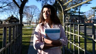 "FILE - In this Feb. 2, 2016, file photo, Naila Amin, 26, holds a book from one of the classes she was taking at Nassau Community College in Garden City, N.Y. According to data provided to The Associated Press, the U.S. approved thousands of requests by men to bring child and teenage brides from another country. ""My passport ruined my life,"" said Naila Amin, a dual citizen from Pakistan who grew up in New York City. She was forcibly married at 13 in Pakistan and applied for papers for her 26-year-old husband to come to the country. ""People die to come to America. I was a passport to him. They all wanted him here, and that was the way to do it."" (AP Photo/Kathy Kmonicek)"