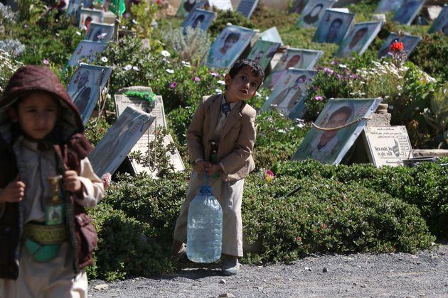 Un enfant yéménite porte de l'eau pour arroser les tombes de ses proches à Sanaa,...