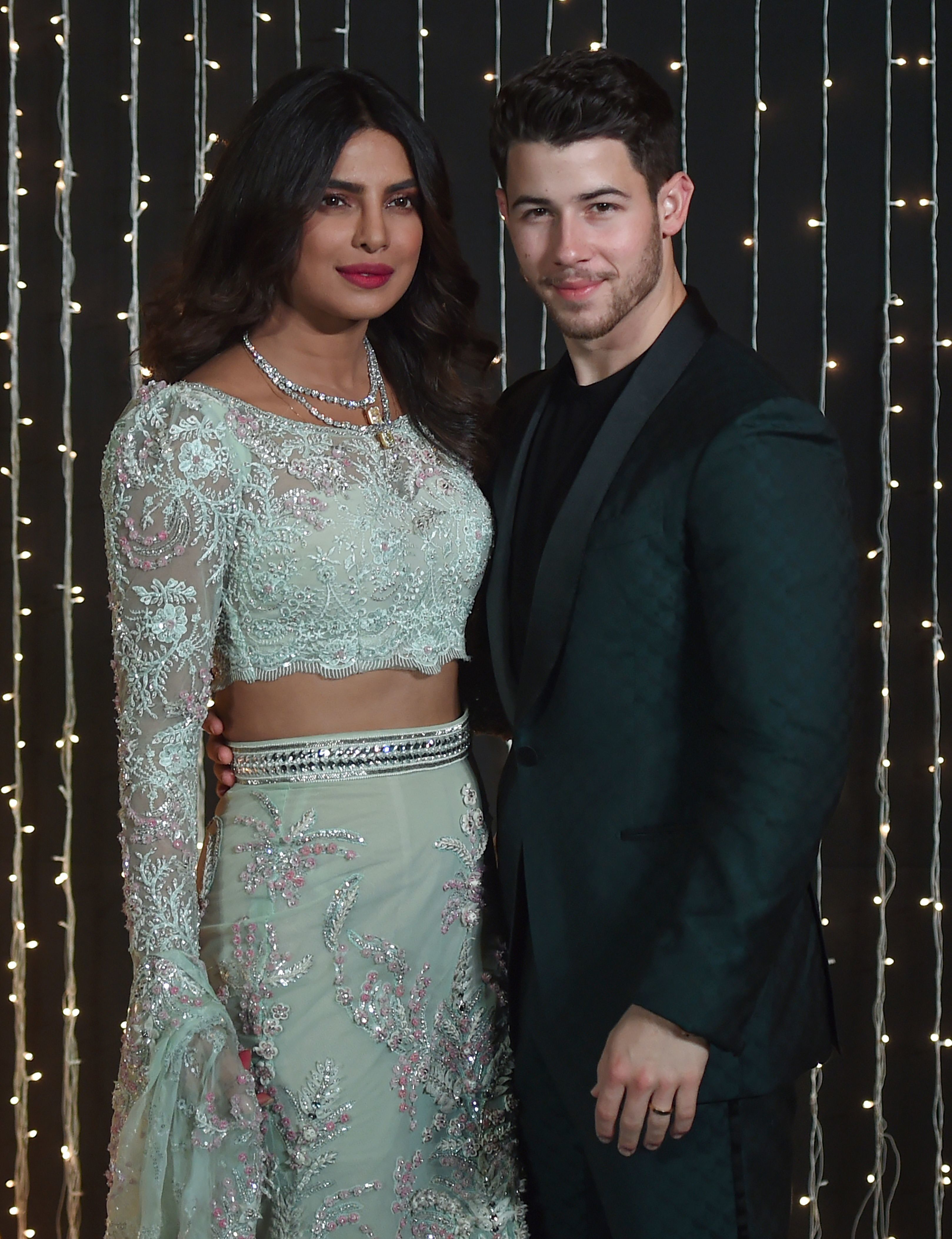 Priyanka Chopra and Nick Jonas pose together at a reception for their wedding in December.