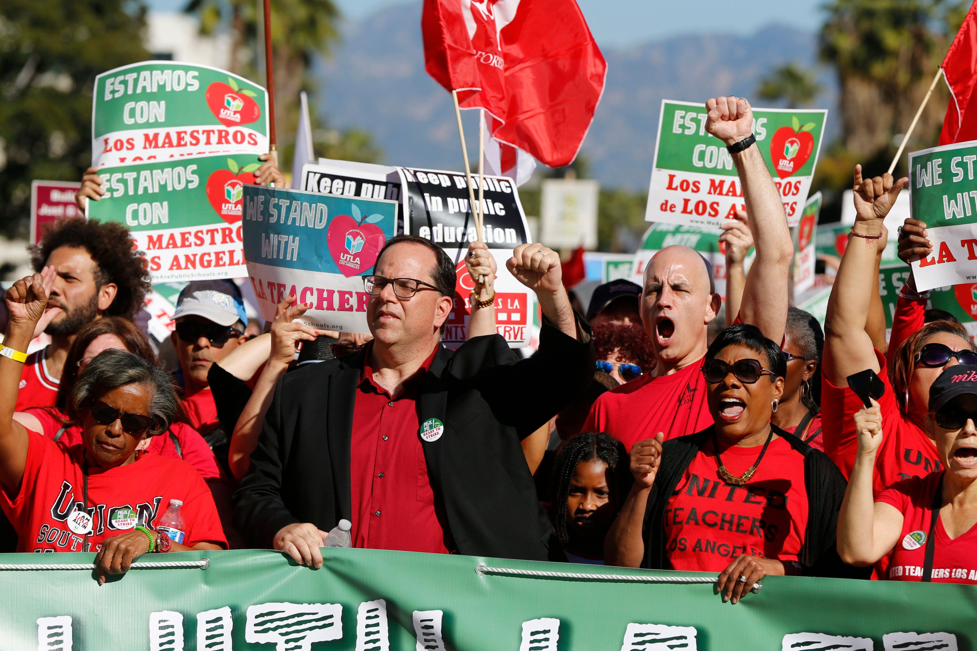 In this Saturday, Dec. 15, 2018 photo, United Teachers Los Angeles President Alex Caputo-Pearl, center, joins teachers at a rally next to the Broad Museum in Los Angeles. Teachers in the nation's second-largest school district will go on strike next month if there's no settlement of its long-running contract dispute, union leaders said Wednesday, Dec. 19. The announcement by United Teachers Los Angeles threatens the first strike against the Los Angeles Unified School District in nearly 30 years and follows about 20 months of negotiations. (AP Photo/Damian Dovarganes