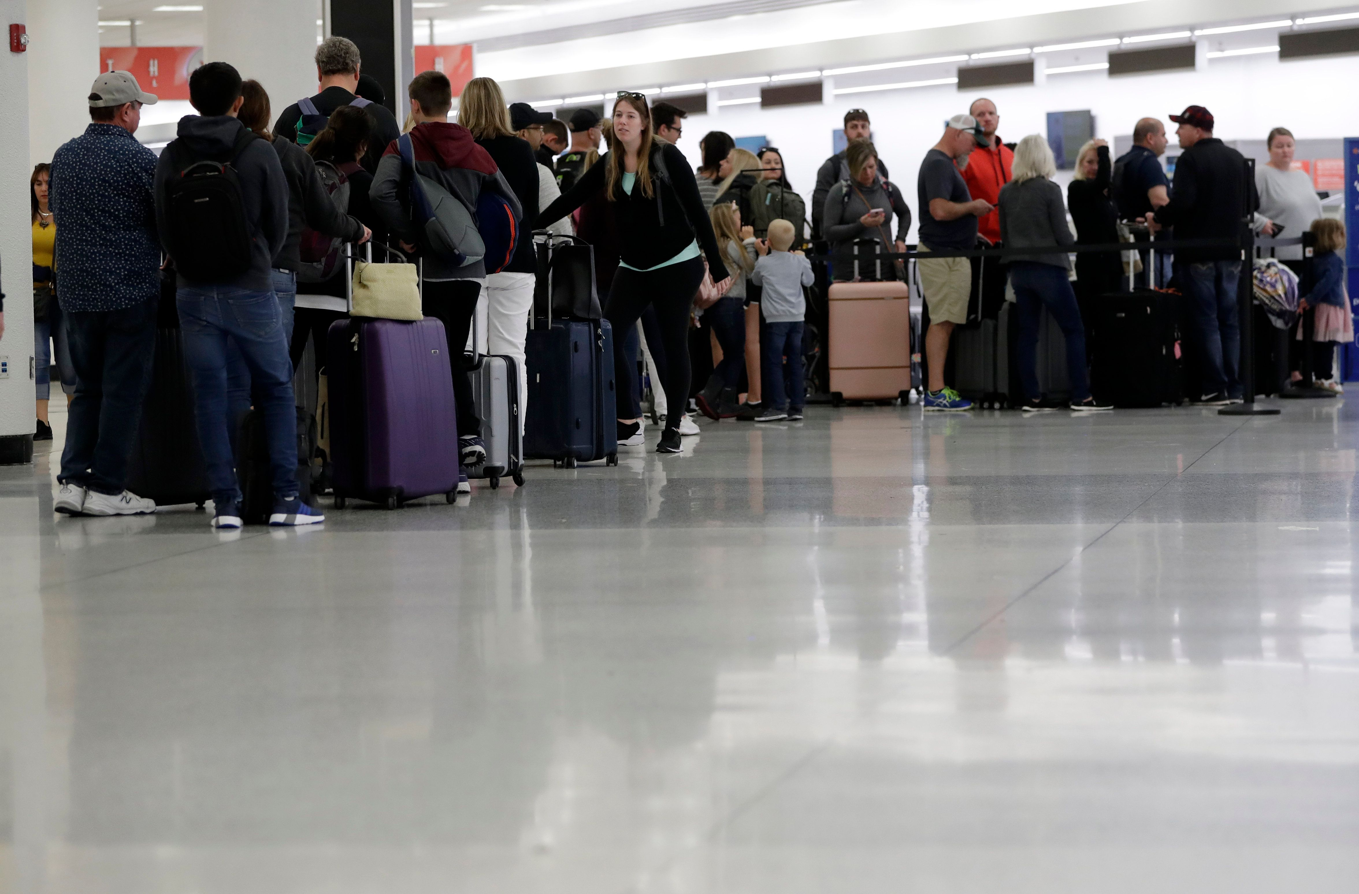 Passengers wait in line at Sun Country Airlines in Terminal G at Miami International Airport, Friday, Jan. 11, 2019, in Miami. The airport is closing Terminal G this weekend as the federal government shutdown stretches toward a fourth week because security screeners have been calling in sick at twice the airport's normal rate. (AP Photo/Lynne Sladky)