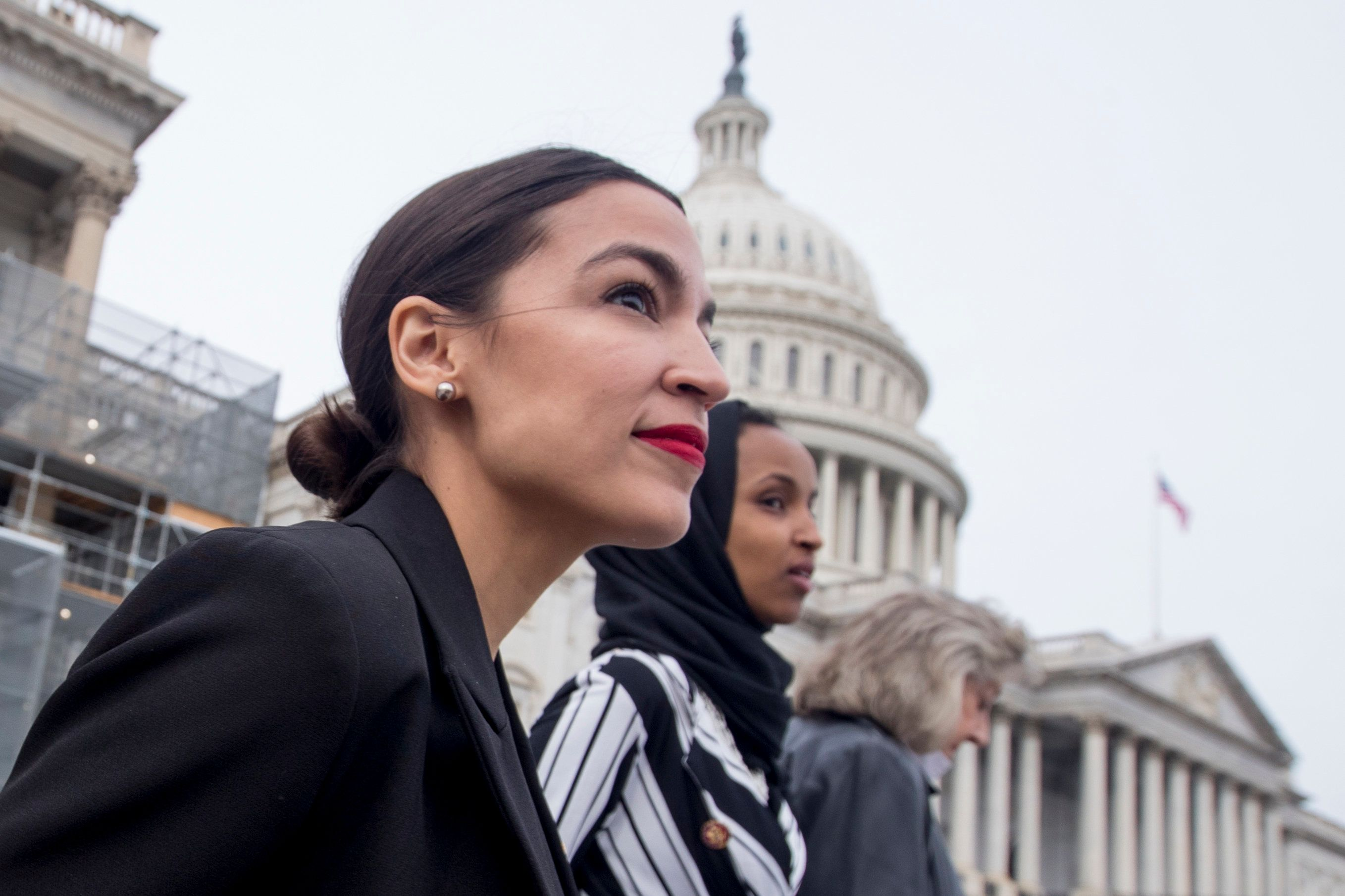 Rep. Alexandria Ocasio-Cortez, left, and D-N.Y., Rep. Ilhan Omar, D-Minn., center, walk down the House steps to take a group photograph of the House Democratic women members of the 116th Congress on the East Front Capitol Plaza on Capitol Hill in Washington, Friday, Jan. 4, 2019, as the 116th Congress begins. Also pictured is Rep. Dina Titus, D-Nev., right. (AP Photo/Andrew Harnik)