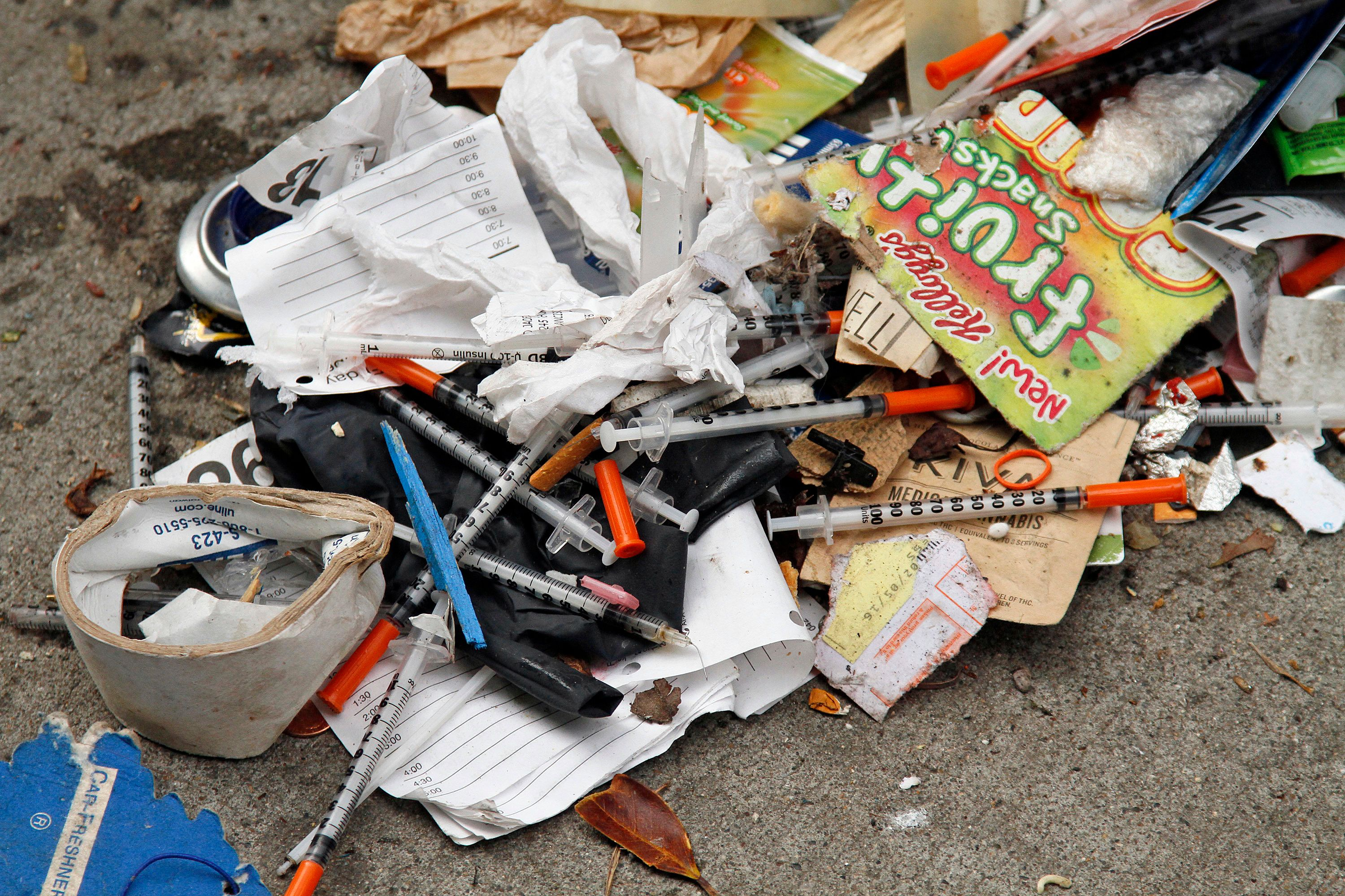 FILE - In this Feb. 26, 2016, file photo, a number of syringes are scattered in the remains of a tent city being cleared by city workers along Division Street in San Francisco. Sean Miller, a 24-year-old transplant, is offering a free app to make it easier for people to report waste - human and otherwise - and used needles and anything else gross on the famously dirty streets of San Francisco. (AP Photo/Eric Risberg, File)