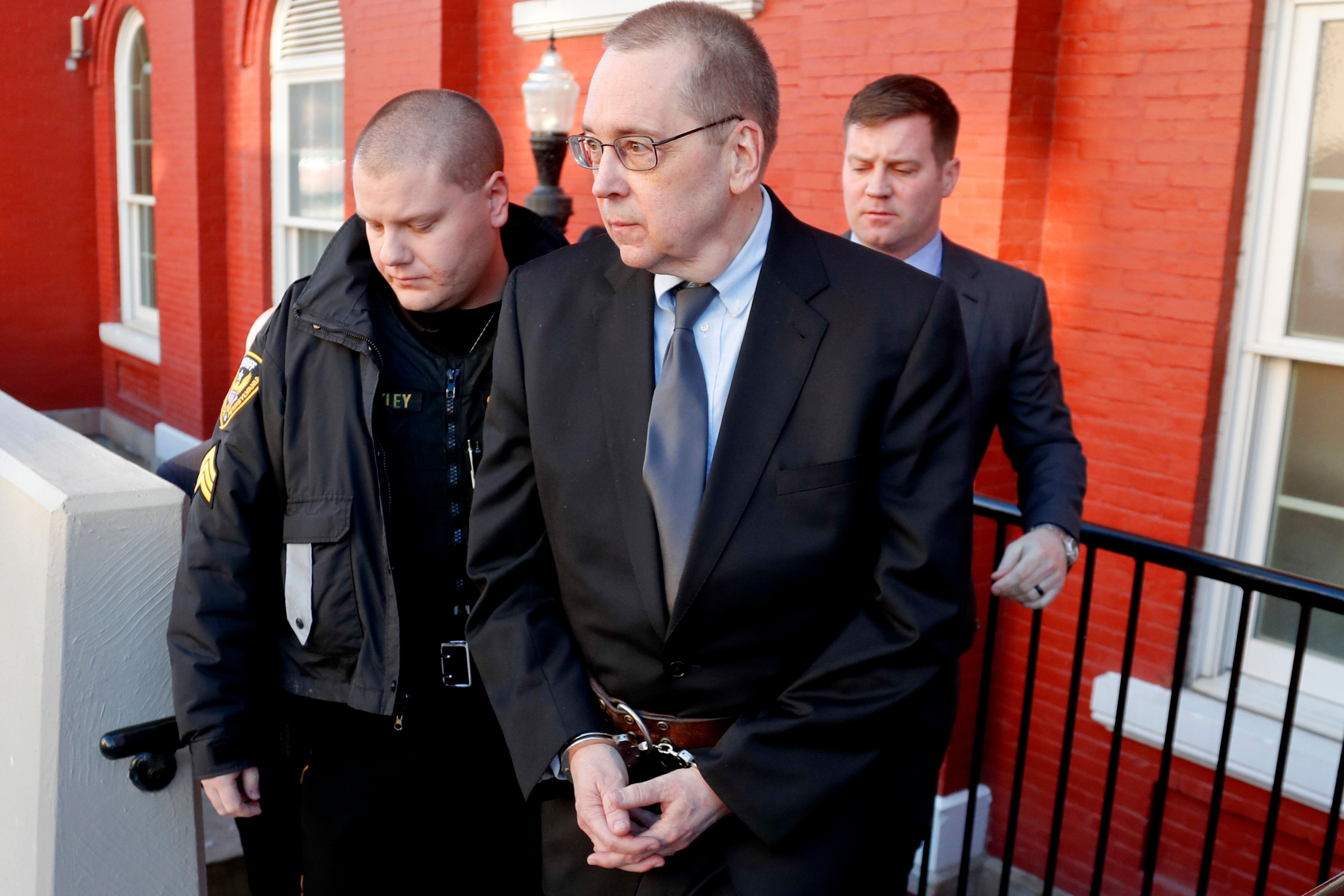 David Lee Poulson, center, a Roman Catholic priest who pleaded guilty to sexually abusing two boys, is taken away from court