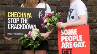 Demonstrators carry placards as they protest over an alleged crackdown on gay men in Chechnya outside the Russian Embassy in London on June 2, 2017.  Russian Foreign Minister Sergei Lavrov on May 30 insisted there were 'no facts' in reports about the persecution of gay men in Chechnya, as he batted away criticism levelled by French leader Emmanuel Macron. Macron on May 29 pressed Russian President Vladimir Putin over an alleged crackdown on gay men in the North Caucasus region of Chechnya as they met for the first time in Versailles.       / AFP PHOTO / Justin TALLIS        (Photo credit should read JUSTIN TALLIS/AFP/Getty Images)