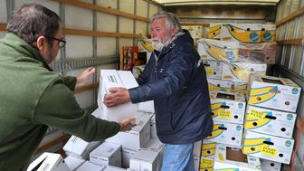 BOSTON, MA - JANUARY 8: Charlie Field, left, and Don Cox prepare to unload boxes of fresh milk in the back of their truck as they arrive in Boston to deliver milk, meat, bread and other food to the US Coast Guard Base in the North End on Jan. 8, 2019. At the base, the partial government shutdown has become more than a long list of impersonal numbers recited in the news media of the furloughed and unpaid, and those in danger of losing benefits. It now is a case, for some members of the worlds most powerful military, of searching for ways to feed their families. On Wednesday, a food pantry stocked by civilians will open on the base to provide free food to Coast Guard members - many with young children - who live paycheck to paycheck and fear they will soon go without pay as the shutdown drags on. Cox is the president of the Massachusetts Military Support Foundation, which will operate the pantry. (Photo by John Tlumacki/The Boston Globe via Getty Images)