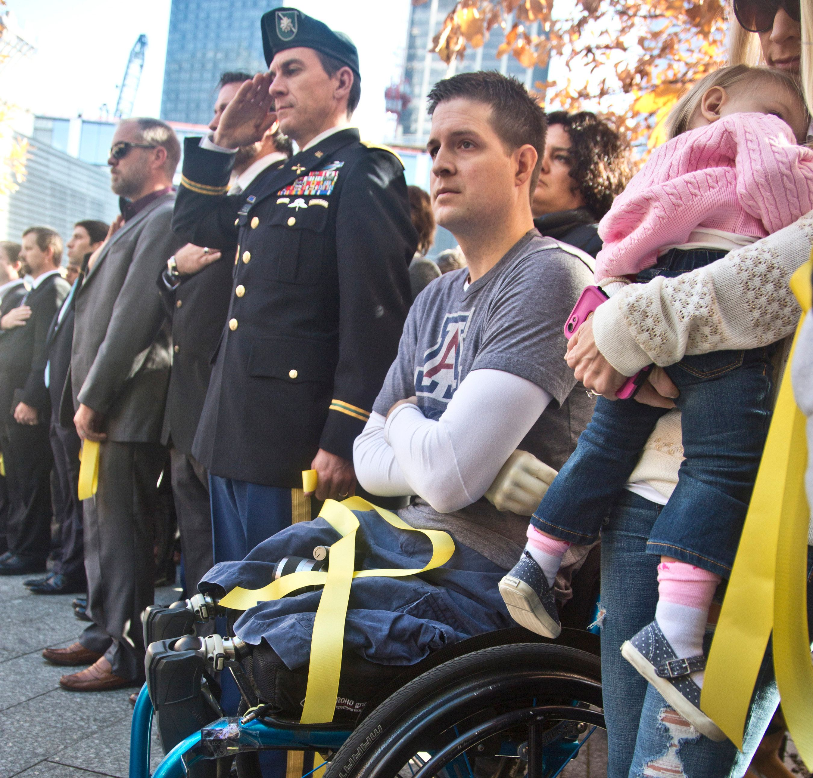"FILE--In this Nov. 10, 2014, file photo, former U.S. Air Force Senior Airman Brian Kolfage, center, sits in a wheelchair next to his wife Ashley, right, who holds their daughter Paris, during the National September 11 Memorial and Museum's ""Salute to Service"" tribute honoring U.S. veterans in New York. Kolfage, a triple-amputee who lost his limbs serving in Iraq in the U.S. Air Force, started a GoFundMe page to help fund construction of President Donald Trump's border wall has already raised millions of dollars. (AP Photo/Bebeto Matthews, file)"