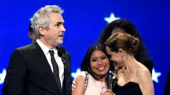 """Alfonso Cuarón (izquierda) acepta el premio a mejor película para """"Roma"""", con las actrices Yalitza Aparicio y Marina De Tavira en segundo plano, en la 24ta edición de los Critics' Choice Awards, el 13 de enero de 2019, en el Barker Hangar en Santa Mónica, California. (Foto de Chris Pizzello/Invision/AP)"""