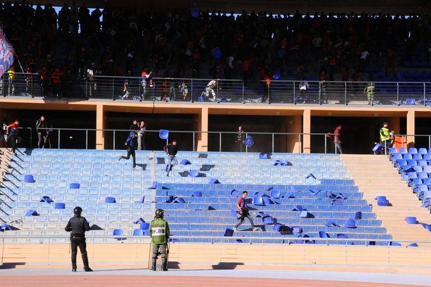 Dans les tribunes, des supporters arrachant et jetant des sièges durant la rencontre opposant...