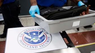 A U.S. Department of Homeland Security seal is seen as a TSA official moves a bin for additional screening at a newly designed passenger screening lane unveiled at Hartsfield-Jackson Atlanta International Airport Wednesday, May 25, 2016, in Atlanta. The new screening lanes allow multiple passengers to load their belongings onto an automated conveyer belt at the same time. The lanes, the first of its kind in the nation, are aimed at speeding up the security process and are modeled on similar systems at London's Heathrow and Amsterdam's Schiphol airports. (AP Photo/David Goldman)