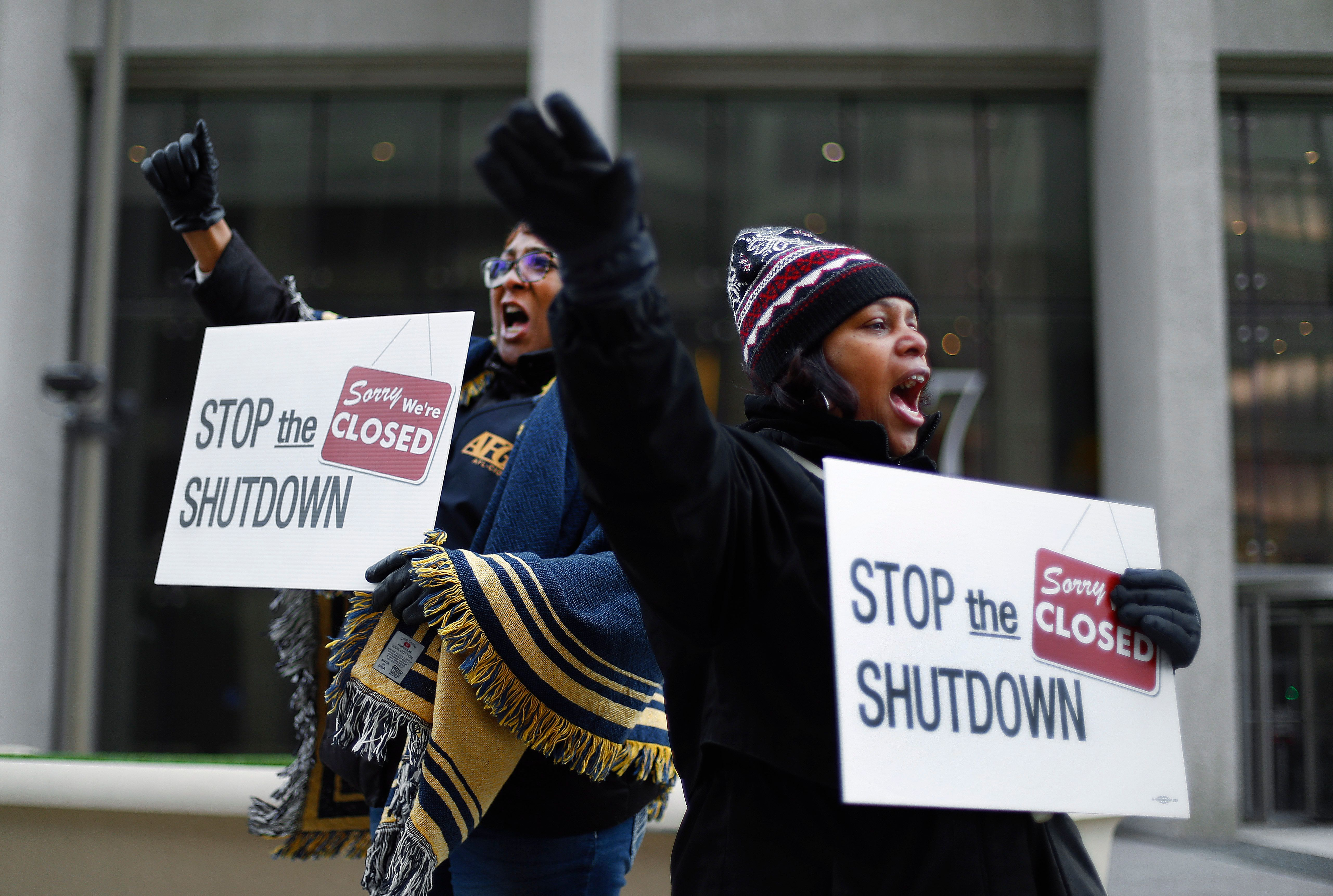 Cheryl Monroe, right, a Food and Drug Administration employee, and Bertrice Sanders, a Social Security Administration employee, rally to call for an end to the partial government shutdown in Detroit, Thursday, Jan. 10, 2019. (AP Photo/Paul Sancya)