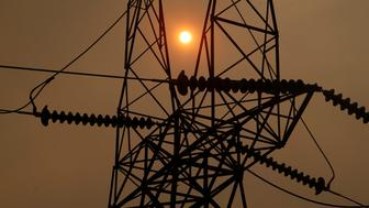 BUTTE COUNTY, CALIFORNIA - NOVEMBER 12: The sun peaks through the smokey skies from the Camp Fire and a PG&E transmission line, Monday, November 12, 2018, three miles west of Pulga, Calif. (Karl Mondon/Digital First Media/The Mercury News via Getty Images)
