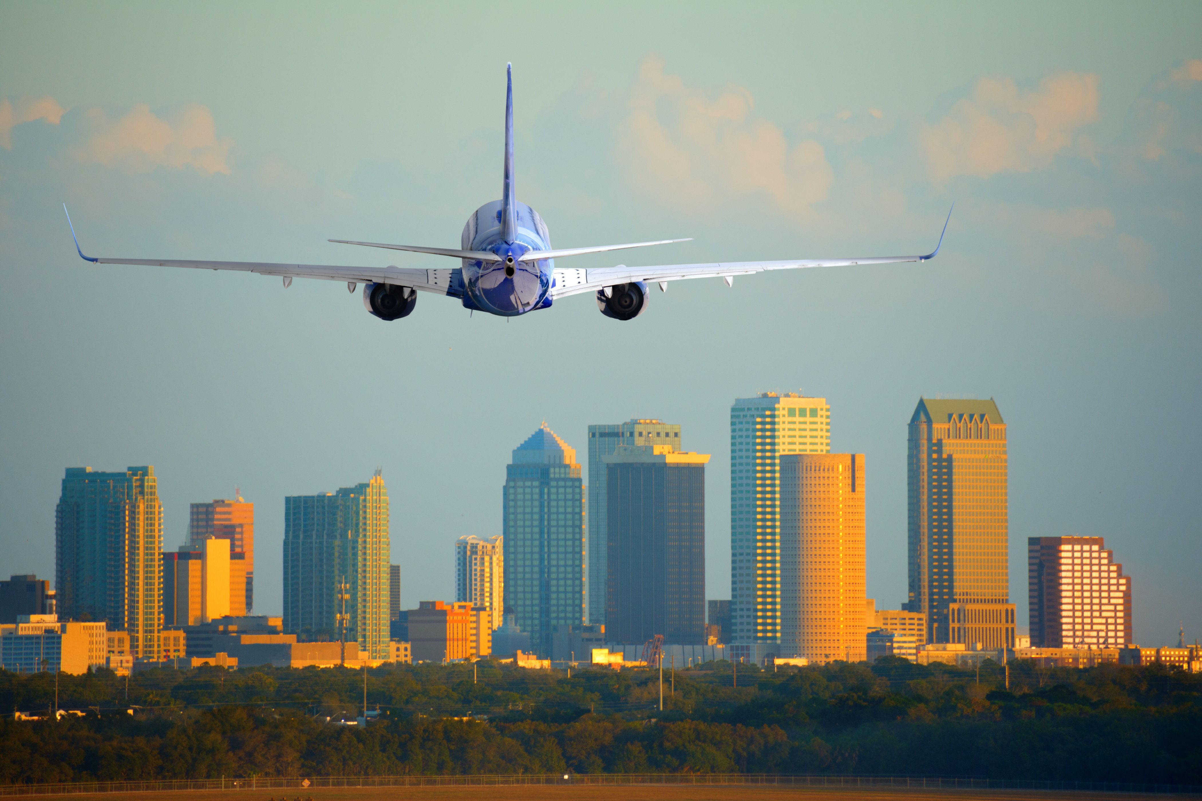 Tampa, Florida, skyline with warm sunset light with a commercial passenger jet airliner plane arriving or departing the International Airport.