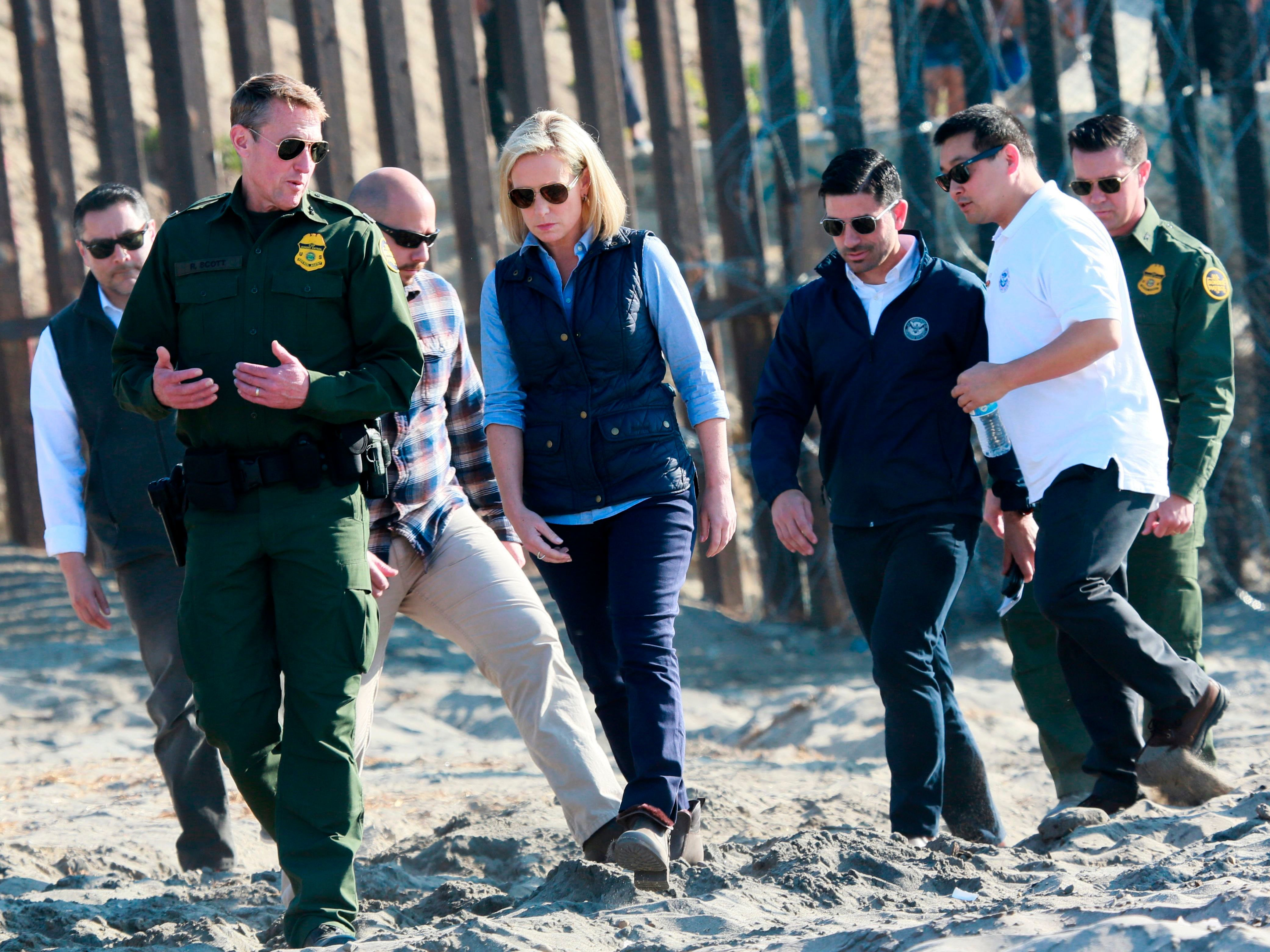 Homeland Security Secretary Kirstjen Nielsen tours the border area with San Diego Section Border Patrol Chief Rodney Scott, left, in San Ysidro, California, on Nov. 20.