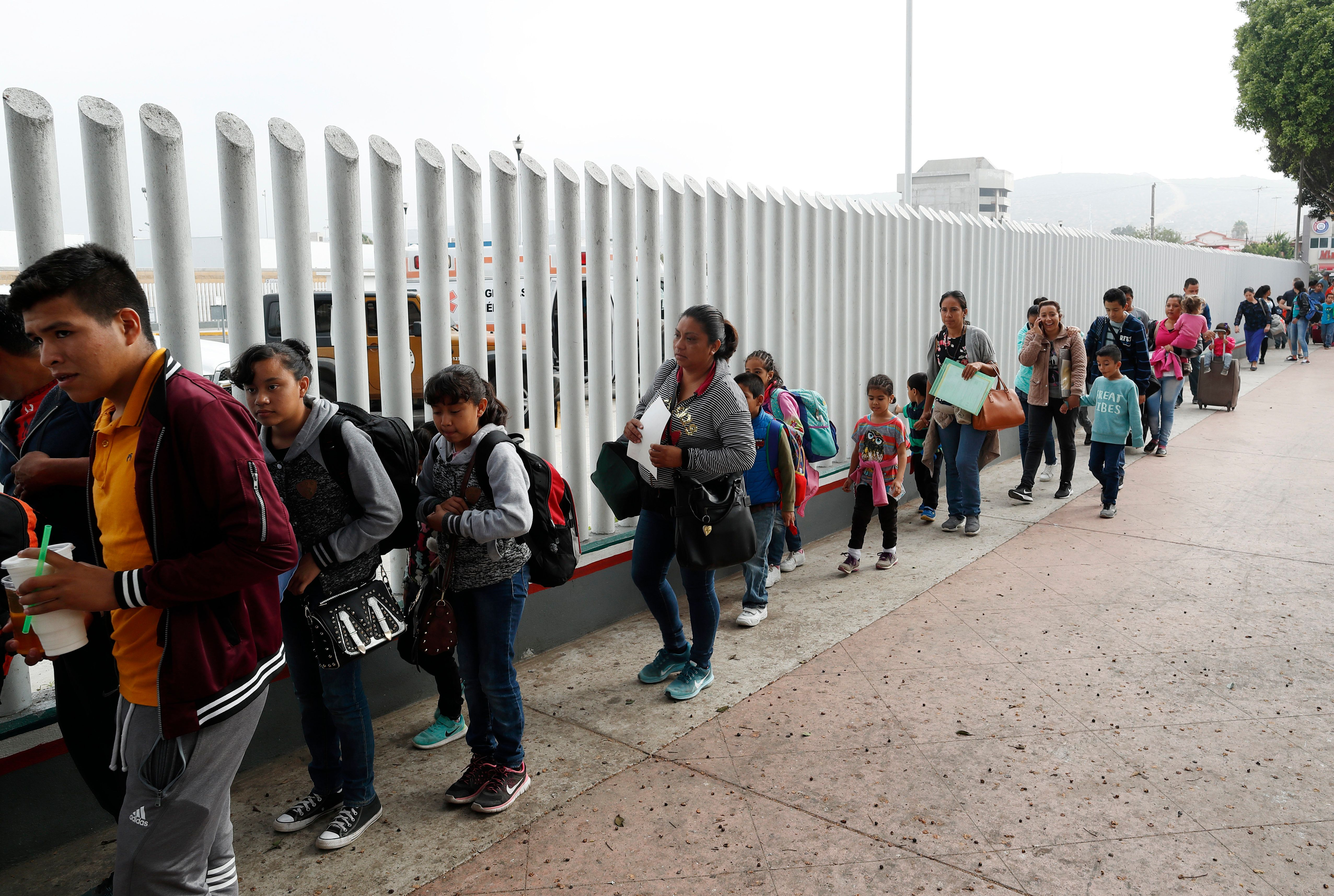 "FILE - In this Thursday, July 26, 2018 photo people line up to cross into the United States to begin the process of applying for asylum near the San Ysidro port of entry in Tijuana, Mexico. A federal judge has extended a freeze on deporting families separated at the U.S.-Mexico border, giving a reprieve to hundreds of children and their parents to remain in the United States. U.S. District Judge Dana Sabraw said in his order Thursday, Aug. 16, 2018, that ""hasty"" deportation of children after reunification with their parents would deprive them of their right to seek asylum. (AP Photo/Gregory Bull,File)"