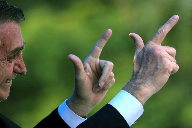 Jair Bolsonaro faz seu habitual gesto que imita armas com as mãos, em evento em