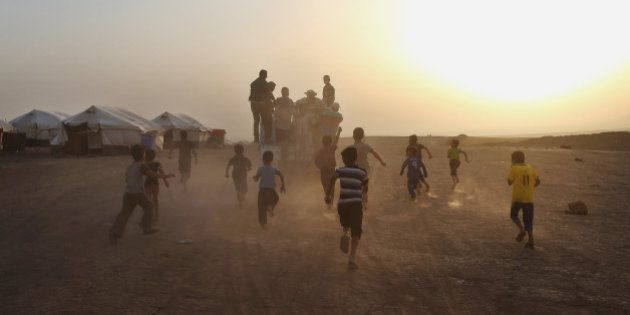 In this Sunday, June 29, 2014 photo, displaced Iraqi boys run behind a truck distributing meals for a...