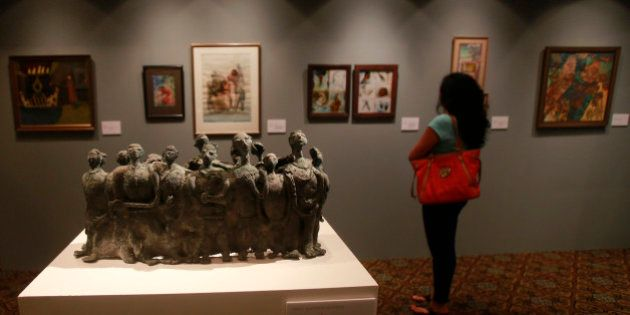 In this photo taken Dec. 16, 2013, a visitor looks at an art work during a media preview of Christie's...