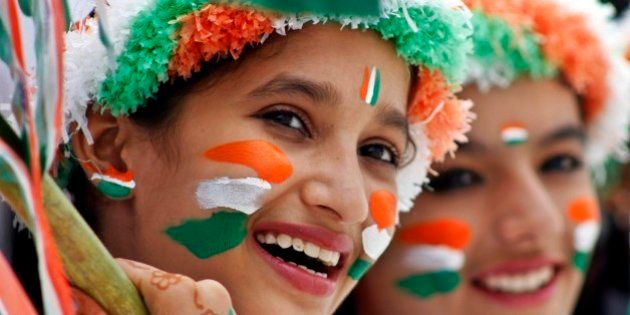 Schoolgirls dressed in the colors of the Indian national tricolor flag participate in rehearsals for...
