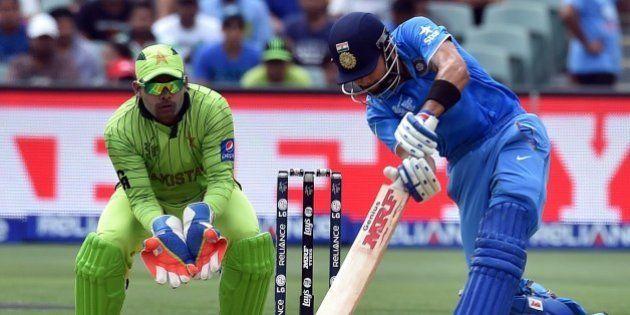 India's batsman Virat Kohli (R) plays a shot as Pakistan's wicketkeeper Umar Akmal (L) looks on during...