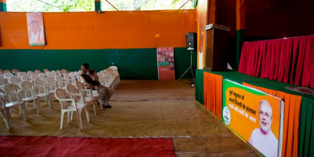 Members of India's leading Bharatiya Janata Party (BJP) sits near an empty stage set up for addressing...