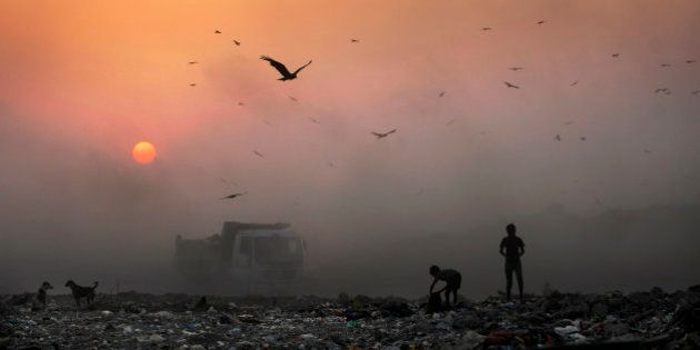 AP10ThingsToSee - A thick blanket of smoke is seen against the setting sun as young ragpickers search...