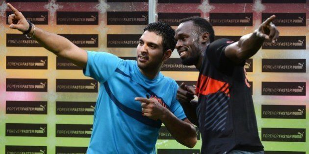 Jamaican Olympic Champion sprinter Usain Bolt (R) and Indian cricketer Yuvraj Singh pose for a photograph...