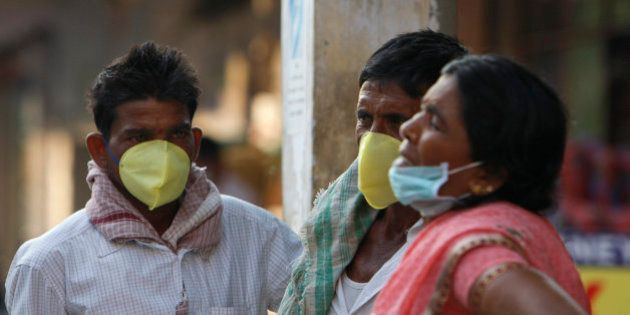 Indians cover their faces with masks as preventive measure against swine flu at the Gandhi Hospital in...