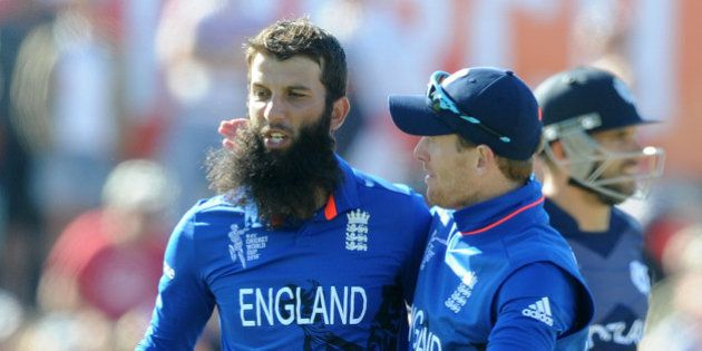 England's Moeen Ali left, is congratulated by his captain Eoin Morgan after taking the wicket of Scotland's...
