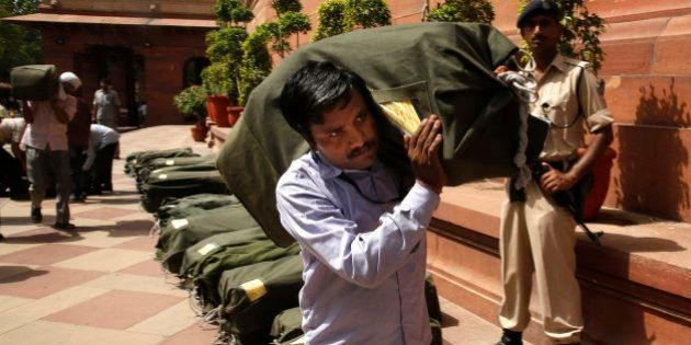 An Indian worker carries a sack containing copies of the 2014-15 union budget at the Indian parliament...