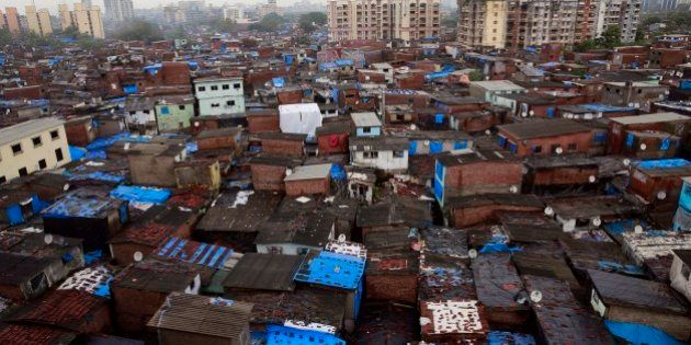 High-rise buildings stand in the background over Dharavi, one of Asia's largest slums, in Mumbai, India,...