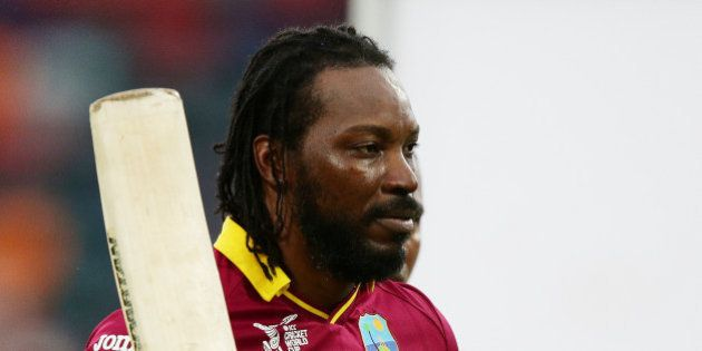 West Indies batsman Chris Gayle waves his bat as he leaves the field after scoring 215 runs during their...