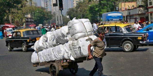 An Indian worker pulls a cart loaded with goods at a traffic intersection in Mumbai, India, Monday, Feb....