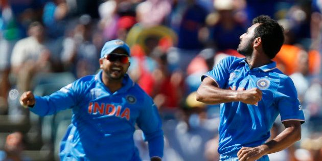 India's Mohammed Shami, right, celebrates with his teammate M S Dhoni after dismissing West Indies batsman...