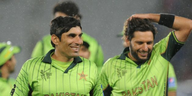 Pakistan's captain Misbah Ul Haq, left, and teammate Shahid Afridi smile as they leave the field after...