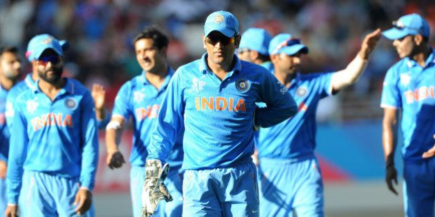 India captain MS Dhoni leads his team from the field after they dismissed Zimbabwe for 287 runs during...
