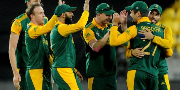 South Africa's Rilee Rossouw is congratulated by teammates after taking a catch to dismiss United Arab...