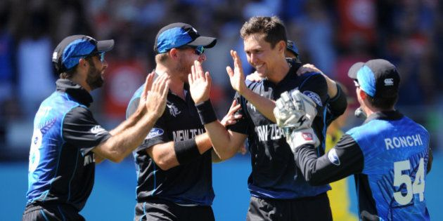 New Zealand's Trent Boult, second right, is congratulated by his teammates after taking the wicket...