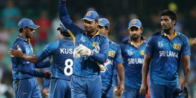 Sri Lanka's Kumar Sangakkara waves to the crowd as he leaves the field after his teams nine wicket loss...