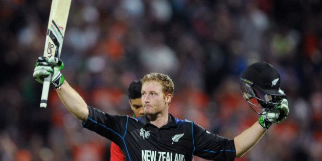 New Zealand's Martin Guptill waves his bat as he celebrates after scoring a century while batting against...