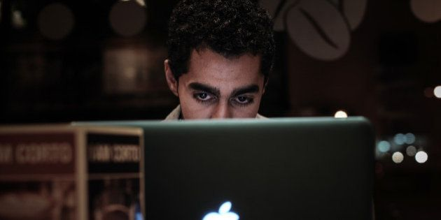 A Bahraini man browses the internet on his laptop in a coffee shop in the capital Manama on January 29,...