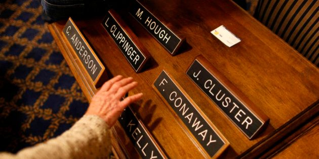 An aide reaches for a name plate for Delegate Kevin Kelly, D-Allegany, before a committee hearing on...