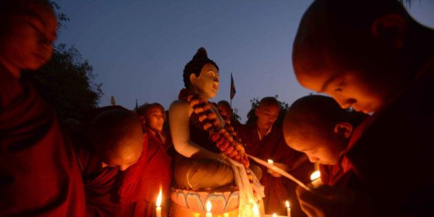 Novice Buddhist monks offer prayers by candle-light for a 16 year old gang rape victim at Tergar Monastery...