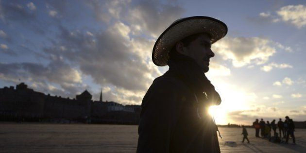 A tourist is pictured on November 1, 2014 on the beach of the Brittany city of Saint-Malo, western France....