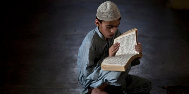 A Pakistani student of a madrassa, or Islamic school, attends a test in reciting verses of the Quran,...