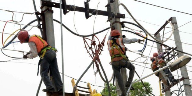 Indian workers install new power cables at the roadside in Amritsar on May 9, 2015. Temperatures are...